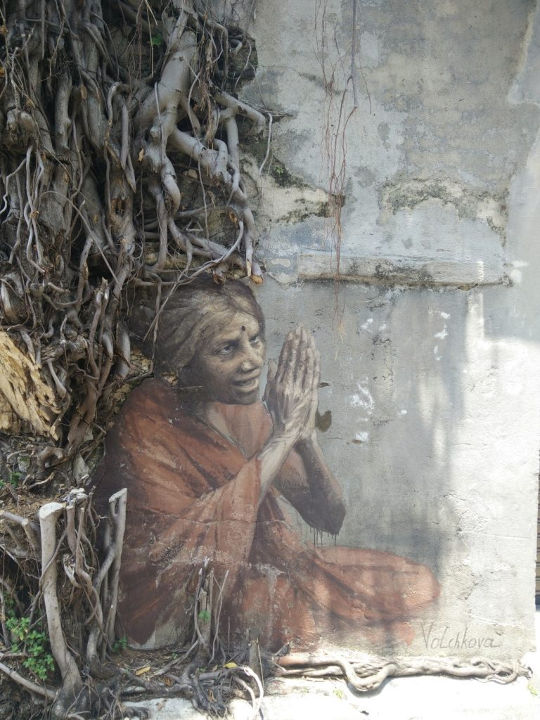 Street art of begging Indian woman.